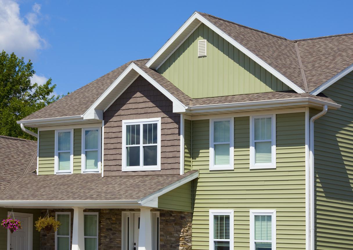Green and Brown House of Stone, Cedar, Vinyl Siding