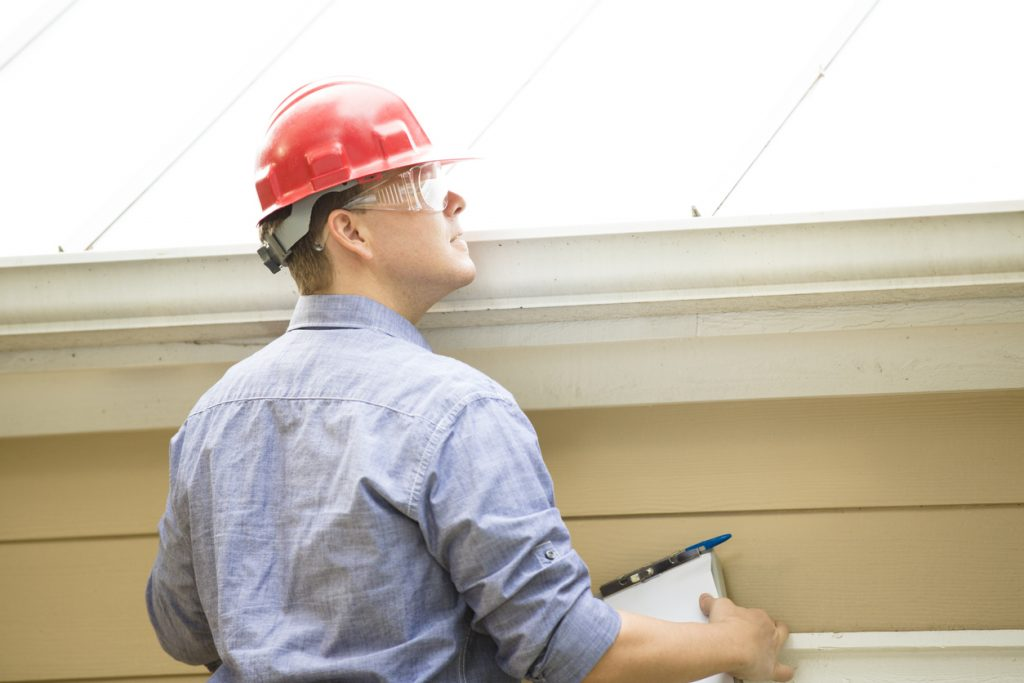 Inspector or blue collar worker examines building roof. Outdoors.